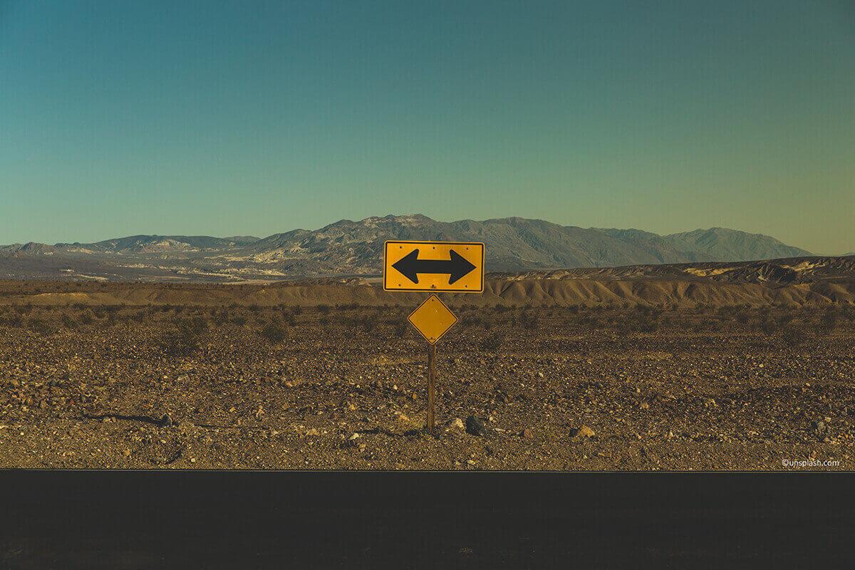 Straßenschild mit Abzweigung. Welchen Weg gehst du? Freiberufler oder Gewerbetreibender?