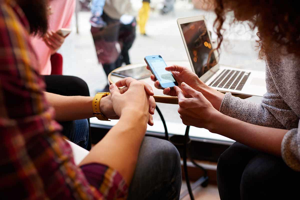 Frau zeigt Freunden ihre Apps