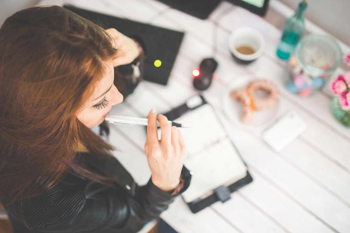 Frau sitzt grübelnd am Schreibtisch