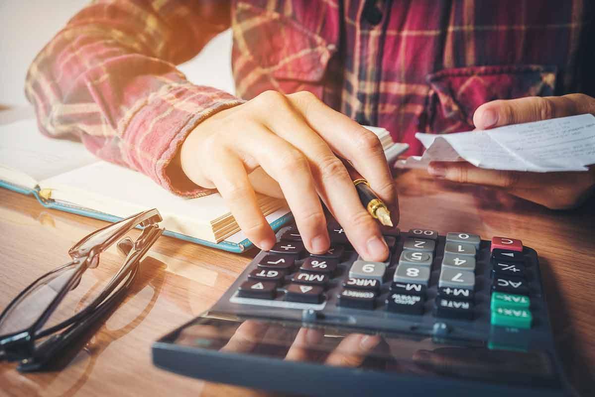 Mann errechnet Skonto mit dem Taschenrechner