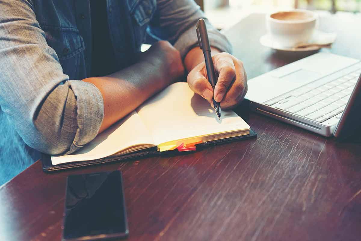 Mann macht sich Notizen zu Rechnungs fristen