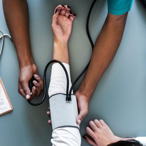 Arzt, der den Blutdruck eines Selbstständige Patienten kontrolliert